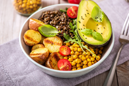 Food bowl with baked potatoes, lentils and spicy chickpeas, avocado, arugula, vegan, vegetarian healthy dinner