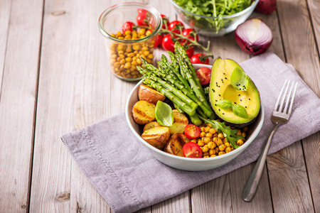 Healthy dinner with green asparagus, lentils and spicy chickpeas, avocado, arugula, vegan, vegetarian healthy food