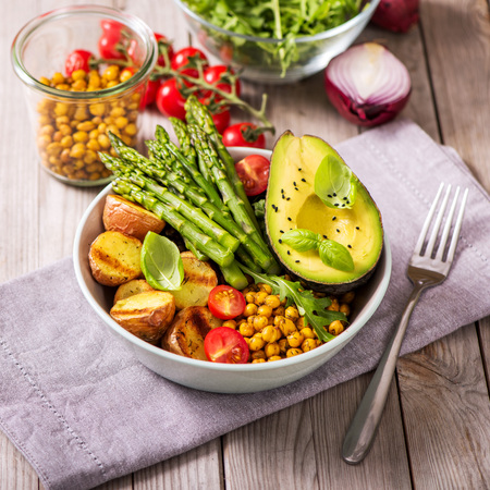 Healthy dinner with green asparagus, lentils and spicy chickpeas, avocado, arugula, vegan, vegetarian healthy food, square image