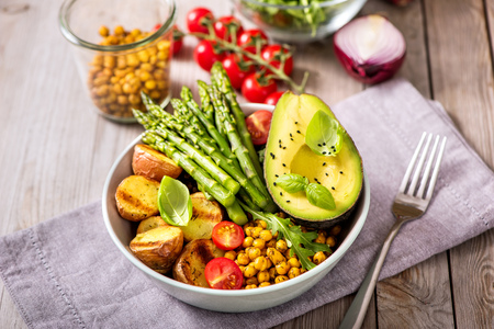 Buddha bowl with green asparagus and baked potatoes, spicy chickpeas, avocado, arugula, vegan, vegetarian healthy food Imagens