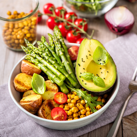 Buddha bowl with green asparagus and baked potatoes, spicy chickpeas, avocado, arugula, vegan, vegetarian healthy food, square image