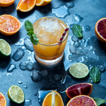 Refreshing cocktail with crashed ice, juicy summer party drink with citrus fruits, square image