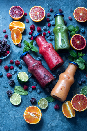 Red, green and yellow smoothies with oranges and mint, healthy vitamin drink in bottles top view Imagens