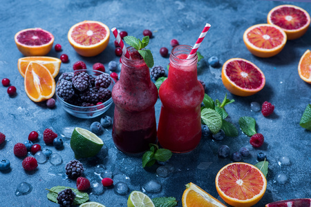 Red smoothie with oranges and mint, healthy vitamin drink in bottles, refreshing juicy cocktail