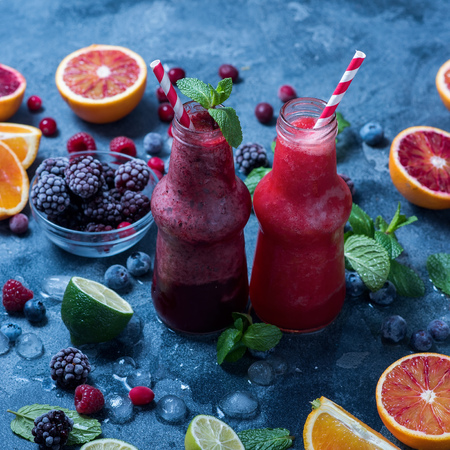Red smoothie with oranges and mint, healthy vitamin drink in bottles, square image Imagens