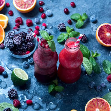 Healthy smoothies in bottles with berries and citrus fruits, vitamin drink, summer refreshment, square image Imagens
