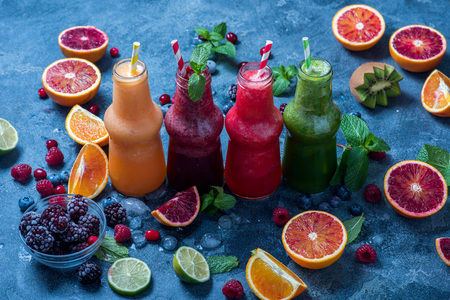 Red, green and yellow smoothies with oranges and mint, healthy vitamin drink in bottles