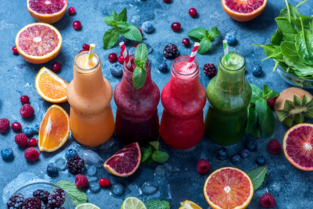 Red, green and yellow smoothies with berries, spinach, oranges and mint, healthy vitamin drink in bottles, diet concept