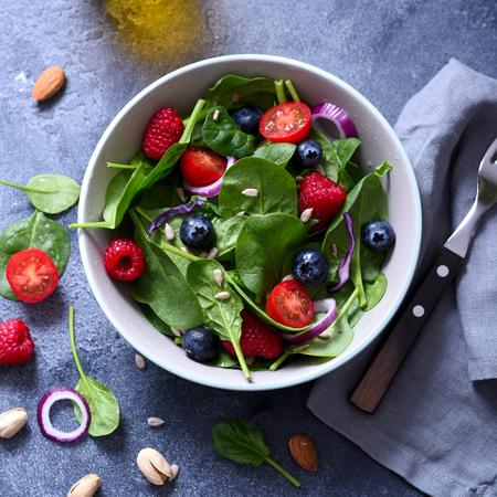 Spinach salad with berries and seeds, healthy lunch, summer snack, raw eating and diet, square image