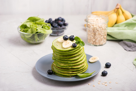 Green pancakes with spinach, blueberries and oats, healthy snack, vegetarian food Imagens - 123584490