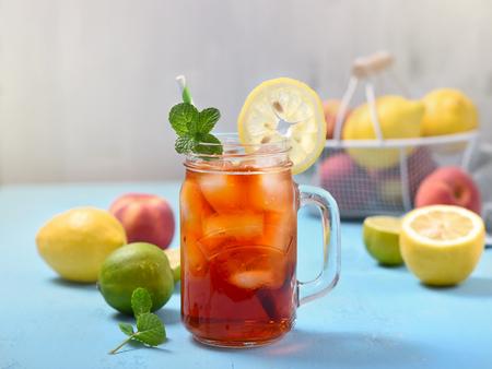 Thé glacé aux citrons, citrons verts et menthe avec glaçons, boisson rafraîchissante d'été, thé aux fruits froid, fond bleu