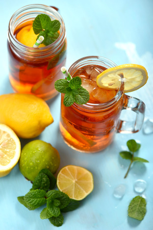 Iced tea with lemons, limes and mint with ice cubes, summer refreshment drink, cold fruit tea,  blue background Banco de Imagens - 123584501