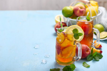 Iced tea with peaches, lemons, limes and mint with ice cubes, summer refreshment drink, cold fruit tea,  copy space background Imagens - 123584509