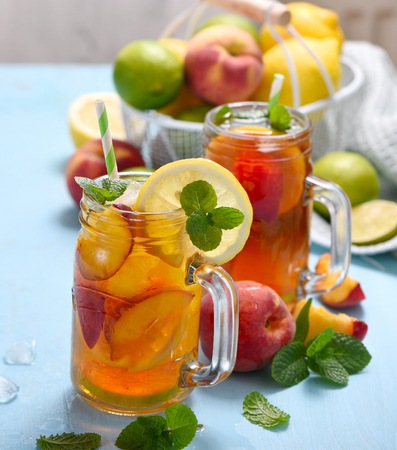 Iced tea with peaches, lemons, limes and mint with ice cubes, summer refreshment drink, cold fruit tea, Banco de Imagens - 123584510