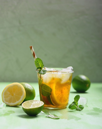 Iced tea, summer refreshment drink or cocktail with lemons and limes, copy space background Imagens - 123584533