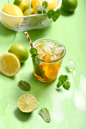 Iced tea, summer refreshment drink or cocktail with lemons and limes, on green background Imagens - 123584534