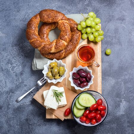 Traditional turkish breakfast with olives, simit bagels, feta cheese, tea, top view, square image, oriental food