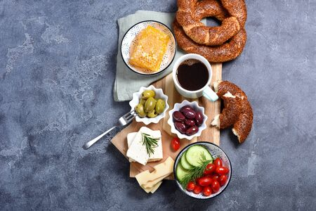 Traditional turkish breakfast with olives, simit bagels, feta cheese, coffee, honey combs, top view, oriental food, copy space background Banque d'images