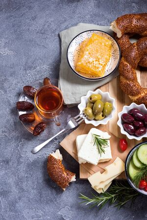 Traditional turkish breakfast with olives, simit bagels, feta cheese, honey, tea and dates, top view, oriental snack