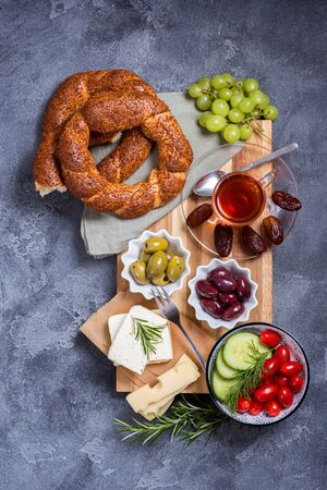 Traditional oriental or turkish breakfast with olives, simit bagels, feta cheese, tea and dates, top view
