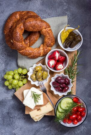 Traditional oriental snack or turkish breakfast with olives, simit bagels, feta cheese, stuffed grape leaves, top view