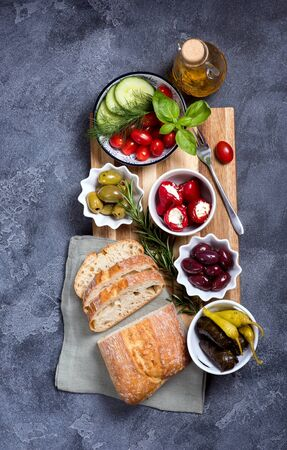 Mediterranean traditional snack with olives, pepperoni, ciabatta, olive oil,  italian or greek food concept, appetizers, antipasti, top view