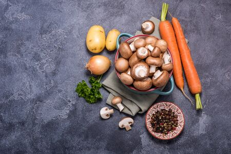 Brown champignons in bowl and vegetables for cooking, ingredients for soup or heatlhy vegan eating, mushrooms, carrots, potaotes and onion over dark background, place for text