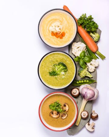 Different vegan cream soups with vegetables, clean eating, dieting and healthy food concept. Fennel and cauliflower soup, mushroom soup and broccoli soup over white background