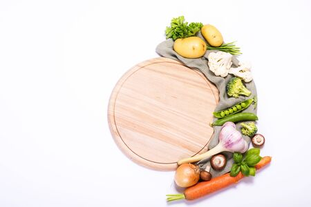 Fresh vegetables for cooking around round empty cutting board, ingredients for healthy eating, copy space white background, place for text, vegan and vegetarian food, recipe and cooking concept