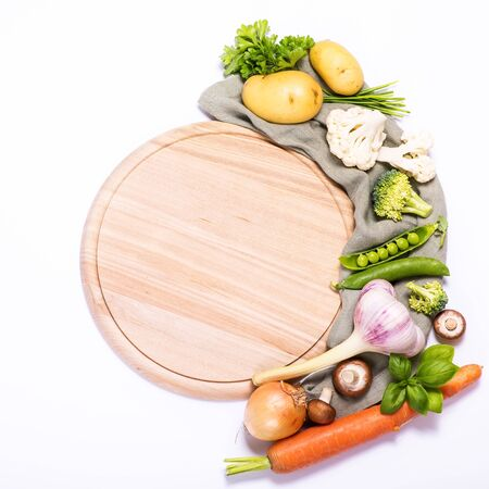 Fresh vegetables for cooking around round empty cutting board, ingredients for healthy eating, copy space white background, place for text, vegan and vegetarian food, recipe and cooking concept, square