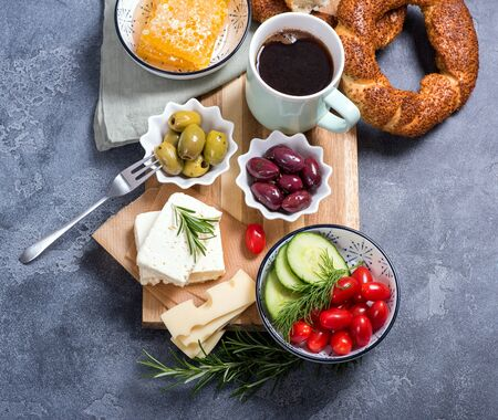 Traditional turkish breakfast with olives, simit bagels, feta cheese, cup of coffee, top view