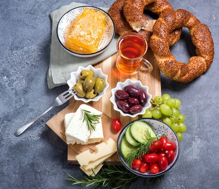Traditional turkish breakfast with olives, simit bagels, feta cheese, tea, top view