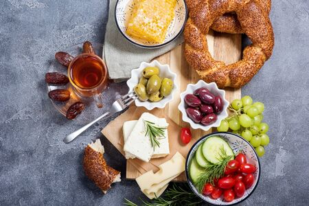 Traditional turkish breakfast with olives, simit bagels, feta cheese, tea with dates, top view