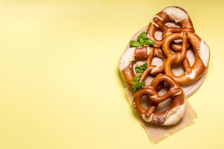 Pretzels on yellow background copy space, german traditional food, european, bavarian snack, oktoberfest concept