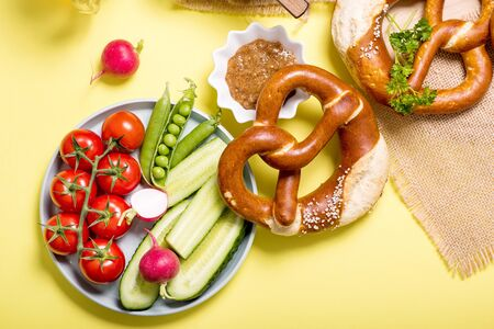 Pretzels and vegetables on yellow background, german traditional food, bavarian snack, european breakfast, oktoberfest concept
