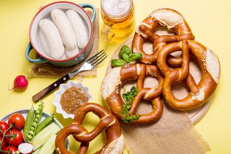 Pretzels, white bavarian sausages, mustard and beer, german traditional food, oktoberfest on yellow background Banco de Imagens