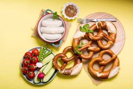Pretzels, white bavarian sausages and vegetables on yellow background, german traditional food, oktoberfest