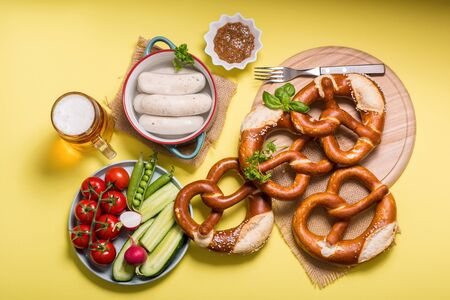 Pretzels, white bavarian sausages, beer, mustard and vegetables on yellow background, german traditional food, oktoberfest