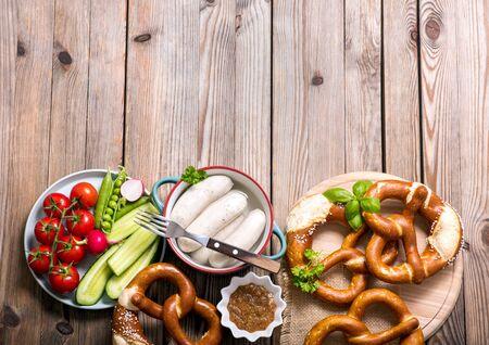 Pretzels, white bavarian sausages, mustard and vegetables on wooden background, german traditional food, oktoberfest copy space background