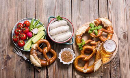 Oktoberfest, german beer festival, pretzels, white bavarian sausages, beer, mustard and vegetables on wooden background, german traditional food,
