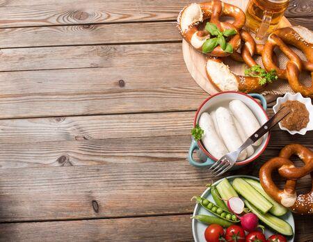 Pretzels, white bavarian sausages, beer, mustard and vegetables on wooden background, german traditional food, oktoberfest copy space background for text Banco de Imagens