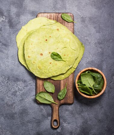 Green tortillas with spinach, round empty flatbreads for wraps, trendy mexican food, healthy snack concept on dark background