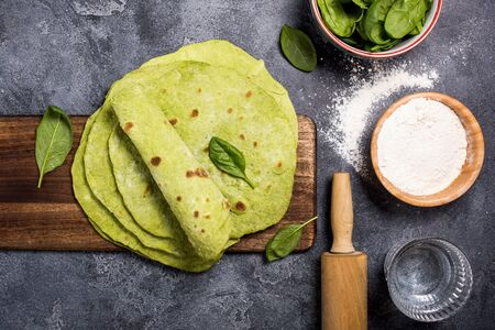 Green tortillas with spinach, cooking ingredients for tortillas, flour, water, spinach and rolling pin, round empty flatbreads for wraps, trendy mexican food, healthy snack concept Banco de Imagens