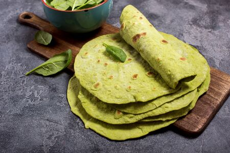 Green tortillas with spinach, tortilla flatbreads for wraps, trendy mexican food, healthy snack concept on dark background Banco de Imagens