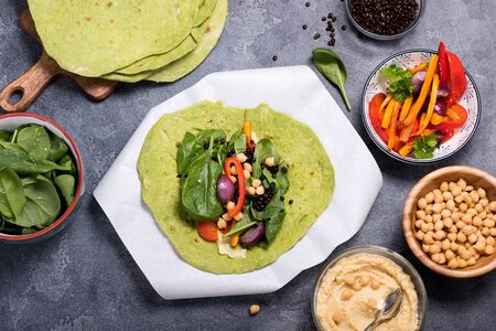 Making vegan tortilla wraps for healthy snack, tortillas with cheakpeas, grilled vegetables hummus, black  lentils, veggies and spinach
