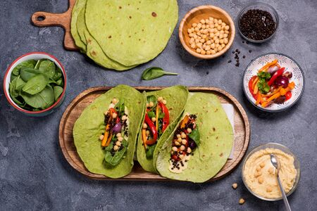 Vegan green tortilla flatbreads or tacos for healthy snack with cheakpeas, hummus, grilled vegetables, beluga lentils and spinach, mexican street food