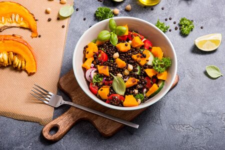Healthy salad with roasted pumpkin, chickpeas and black lentils, autumn food, vegan food, clean eating concept