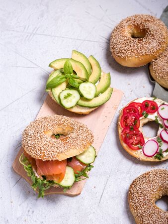 Bagel sandwiches with avocado, salmon, egg and vegetables, healthy snack or brunch, top view, brunch or breakfast idea