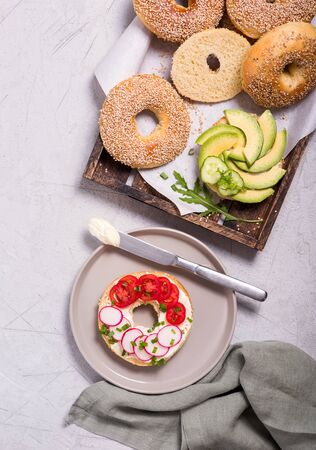 Bagel sandwiches with avocado, tomatoes and cream cheese, healthy snack, top view, brunch or breakfast food