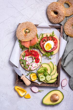 Bagel sandwiches with avocado, salmon, egg and vegetables, healthy snack, brunch or breakfast, top view